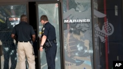 Police officers enter the Armed Forces Career Center through a bullet-riddled door after a gunman opened fire on the building in Chattanooga, Tennessee, July 16, 2015.