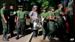 A Sri Lankan municipal worker, center, along with army soldiers leave for Dengue fever eradication work in Colombo, Sri Lanka, July 4, 2017.
