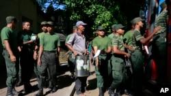 FILE - Seorang pegawai pemerintah Sri Lanka (tengah) bersama dengan tentara bersiap untuk melakukan pemberantasan Demam Berdarah di Colombo, Sri Lanka, July 4, 2017.