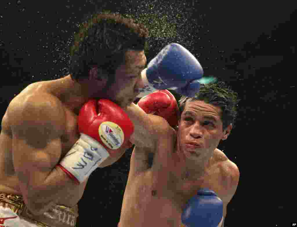 Japanese champion Akira Yaegashi, (l), gets a punch from Mexican challenger Edgar Sosa in the 10th round of their WBC flyweight boxing title bout in Tokyo. Yaegashi defended his world title by a unanimous decision.