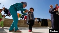 28일 레바논 남부 세바의 시리아 난민촌에서 한 소녀가 소아마비 의심 증세를 보이는 동생을 돕고 있다.