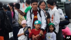 A father and his children who survived the massive Typhoon Haiyan, wait for an evacuation flight on the tarmac of the airport in Tacloban, Philippines, Nov. 21, 2013.