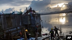 A rescue team wades into flood waters to retrieve a body in Tacloban, central Phillipines, Nov. 13, 2013.