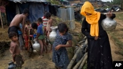 FILE - Rohingya Muslims collect water from a tube well at a refugee camp at Cox's Bazar Ukhia area, Bangladesh, Sept. 9, 2017.
