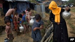 Rohingya Muslims collect water from a tube well that was installed a few days ago at new refugee camp at Cox's Bazar Ukhia area, Bangladesh, Sept. 9, 2017.