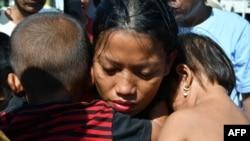 Susi Rahmatia, 26, memeluk anak keduanya (kanan) dan Jumadil (kiri), 5, setelah hilang selama tujuh hari, di sebuah pengungsian di Palu, 5 Oktober 2018. Susi mengira anaknya meninggal, tapi pada hari Jumat, seminggu setelah mereka terpisah akibat gempa dan tsunami, mereka kembali bertemu.