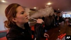 FILE - Talia Eisenberg, co-founder of the Henley Vaporium, uses her vaping device in New York, Feb. 20, 2014.