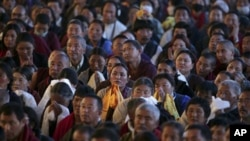 Buddhist devotees listen to the Tibetan spiritual leader the Dalai Lama, unseen, as he addresses Tibetan devotees during the Kalachakra Buddhist festival in the town of Bodh Gaya, believed to be the place where Buddha attained enlightenment, Bihar, India,