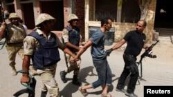 Mısır güvenlik güçleri Kahire'den 14 km uzaklıktaki Kerdasah kentinde düzenledikleri operasyon sonunda bir şüpheliyi tutukluyor.