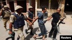 Pasukan keamanan menangkap seorang tersangka (dua dari kanan) di Kerdasah, kota kecil yang terletak sekitar 14 kilometer dari Kairo, Kamis (19/9).