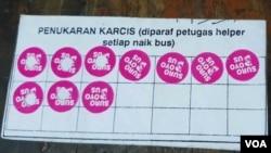 Kartu dengan sticker khusus diberikan kepada masyarakat setelah menukar sejumlah gelas dan botol plastik bekas, petugas akan melubangi sticker dan mengganti dengan tiket Suroboyo Bus (Petrus/VOA).
