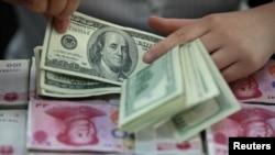 一名银行工作人员在点算美元和人民币。(资料照)