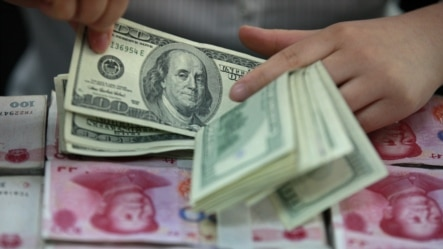 一位中国的银行出纳员在一堆人民币百元大钞上清点美元