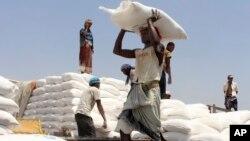 FILE - Men deliver U.N. World Food Programme (WFP) aid in Aslam, Hajjah, Yemen, Sept. 21, 2018.