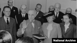Bess and Margaret Truman stand beside Harry Truman as he takes the oath of office.