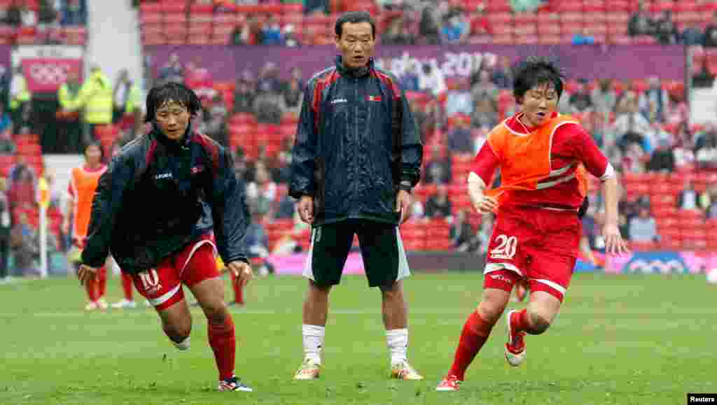 North Korea's Yun Hyon-hui and Yong Sim-choe warm up before their women's football first round Group G match against the U.S.