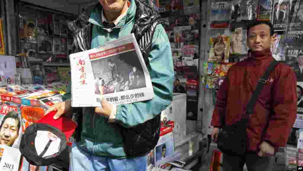 2013年1月10日,一位男士在广州《南方周末》总部附近的一处报刊亭展示最新版的《南周》。