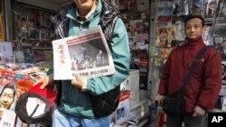 Seorang warga di Guangzhou menunjukkan edisi terbaru harian Southern Weekly setelah berakhirnya pemogokan para wartawan (10/1).