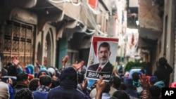 រូបភាពឯកសារ៖ អ្នកគាំទ្រប្រធានាធិបតី Mohamed Morsi នៃជនជាតិឥស្លាម ស្រែកពាក្យស្លោកនិងលើករូបថតលោកនៅទីក្រុង Cairo ប្រទេសអេហ្ស៊ីប។