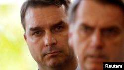 Flavio Bolsonaro, son of Brazil's President-elect Jair Bolsonaro is seen behind him at the transition government building in Brasilia, Nov. 27, 2018.
