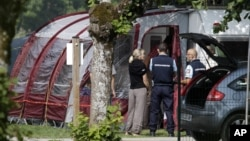 Gendarmes and investigators stand at the camp site where the slain British family were holidaying in Saint Jorioz, near Annecy, September 6, 2012.