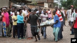Men carry a dead body in the Nyakabiga neighborhood of Bujumbura, Burundi, where a number of people were found shot dead a day after the government said an unidentified group had carried out coordinated attacks on three military installations, Dec. 12, 2015.