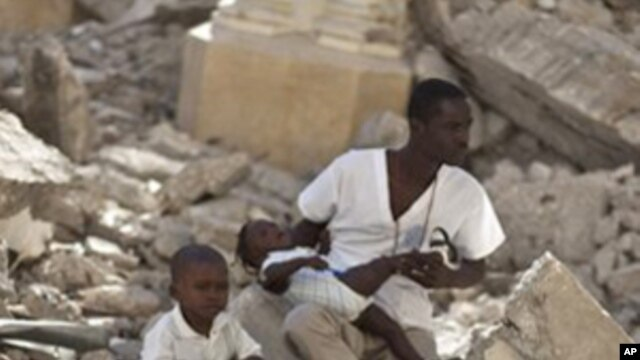 A man with two children sits in the rubble of the earthquake-damaged Cathedral during a mass in Port-au-Prince, Haiti, Jan. 12, 2011.