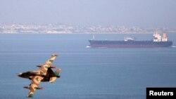 ایرانی فضائیہ کا ایک طیارہ خلیجِ عمان میں پرواز کر رہا ہے جب کہ پسِ منظر میں ایک آئل ٹینکر لنگر انداز ہے۔ (فائل فوٹو)
