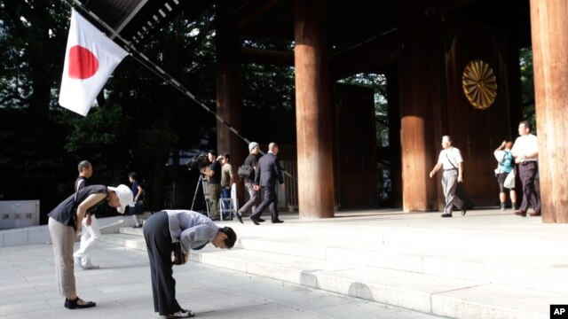 FILE - People bow deeply at the Yasukuni Shrine in Tokyo, August 15, 2013.