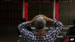 An investor reacts near boards displaying stock market prices in Beijing, China, Dec. 6, 2018.