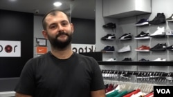 Taylan Akcora, who owns a chain of sports shoe shops, fears that price hikes will be necessary as the value of Turkey's currency falls. (D. Jones/VOA News)