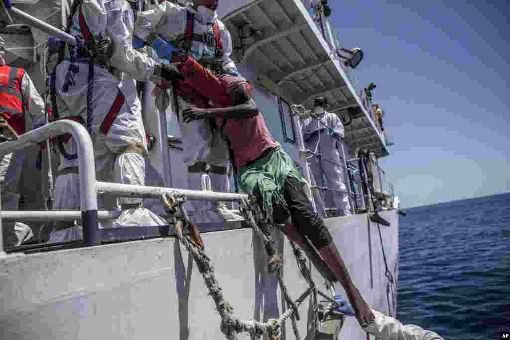 A migrant is pulled up onto a vessel by members of the Italian Coast Guard in the central Mediterranean Sea.