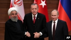 Iran's President Hassan Rouhani, left, Russia's President Vladimir Putin, right, and Turkey's President Recep Tayyip Erdogan lock hands during a group photo in Ankara, Turkey, Wednesday, April 4, 2018.
