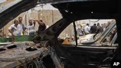 People gather at the scene of a bomb attack in Baghdad's Shiite enclave of Sadr City, Iraq, Monday, July 23, 2012.