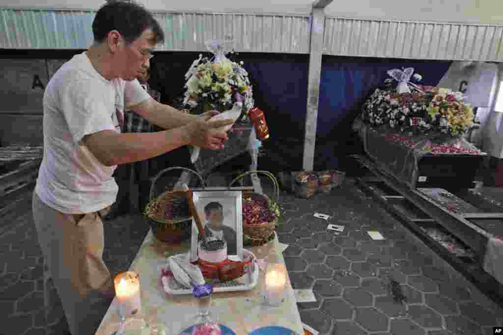 A relative holds a dove near the coffins of victims of AirAsia Flight 8501 during their cremation in Surabaya, East Java, Indonesia, Jan. 8, 2015.