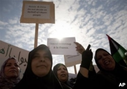 """利比亚妇女在班加西集会高举英语标语牌,上写""""俄国中国不代表利比亚人民""""和""""多谢法国""""(3月23日)"""