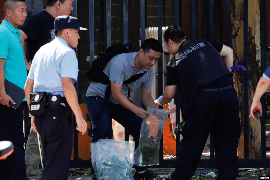 """安全人員和調查人員於2018年7月26日在北京的美國大使館外爆炸現場工作。 北京警方就當天下午美國大使館外的爆炸拘捕了一名嫌疑人。 警方表示,一名26歲來自內蒙古的薑姓男子"""" 在朝陽區天澤路和安家樓路十字路口,點燃一疑似爆竹裝置後,發生爆燃""""。 警方沒提到事情發生在美國大使館外東南角。 美國大使館把這個裝置稱為""""炸彈""""。 美國大使館表示:""""除了引爆者本人,沒有人員在爆炸中受傷,爆炸也沒有造成大使館財產的損失。 """""""