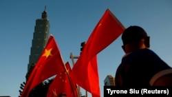 Pendukung Pro-China mengibarkan bendera nasional China di depan gedung landmark Taipei 101, di Taipei, Taiwan 22 Agustus 2016. (Foto: REUTERS/Tyrone Siu)