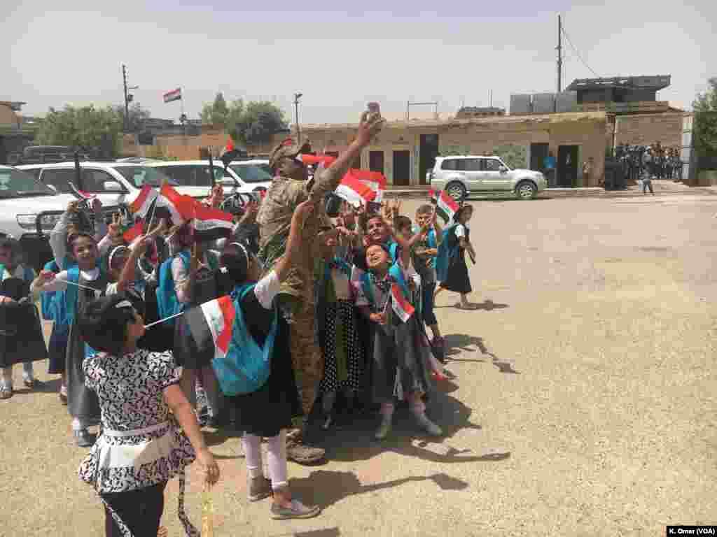 Seorang tentara Irak sedang berswafoto dengan para pelajar Sekolah Dasar Belqis (bagian kanan Mosul) 18 Juli 2017.
