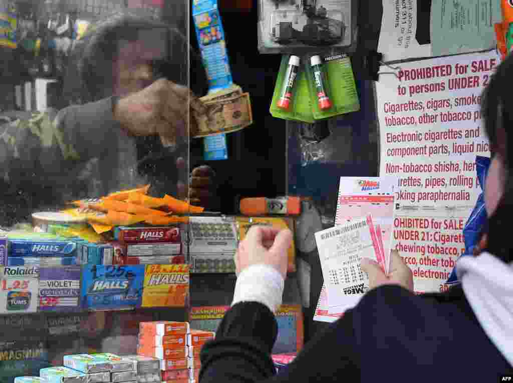 A woman (R) purchases Mega Millions lottery tickets in New York City, US. The Mega Millions jackpot currently is up to $970 million.