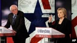 Hillary Rodham Clinton, kanan, saat debat bakal calon presiden Partai Demokrat, sementara Bernie Sanders mendengarkan di Des Moines, Iowa, 15 November 2015.