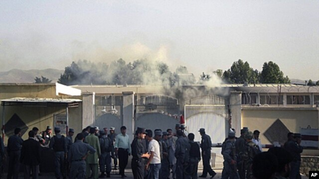 Afghan security stand outside the provincial governor's compound as smoke is seen rising from inside in Taloqan, Takhar province, north of Kabul, Afghanistan, May 28, 2011