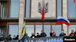 Những người biểu tình ủng hộ Nga treo một biểu ngữ và phất cờ sau khi vào tòa nhà chính phủ ở Donetsk, 6/4/14