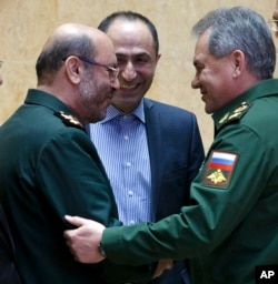 FILE -- Russian Defense Minister Sergei Shoigu, right, and Iranian Defense Minister Hossein Dehghan shake hands during a meeting in Moscow, Russia, Feb. 16, 2016.