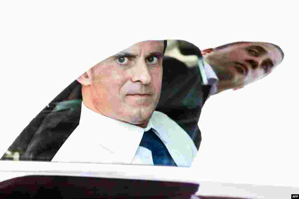 France's Interior Minister Manuel Valls looks through a car window, as one of his bodyguards is reflected, in Cayenne's Mango neighborhood during a three-day visit in the French overseas department of Guiana, Mar. 7, 2013.