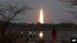 People watch as Indian Space Research Organization's Geosynchronous Satellite Launch Vehicle Mk III rocket lifts off from the space launch center in Sriharikota, India, June 5, 2017.