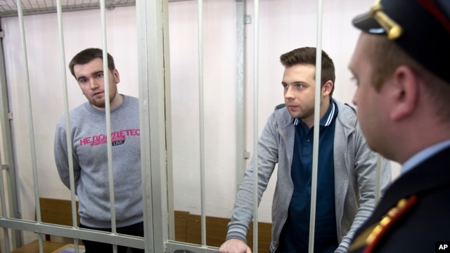 FILE - Opposition activists Alexei Gaskarov (L) and Ilya Gushchin (C) stand behind bars in a court room before hearings against opposition activists detained on May 6, 2012, during a rally at Bolotnaya Square, in Moscow, Russia, Thursday, April 24, 2014.