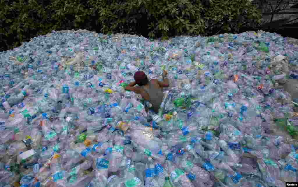 A worker uses a rope to move through a pile of empty plastic bottles at a recycling workshop in Mumbai, India.