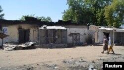 Dua perempuan Nigeria melewati rumah-rumah yang hangus akibat serangan militan Boko Haram bulan lalu (foto: dok).