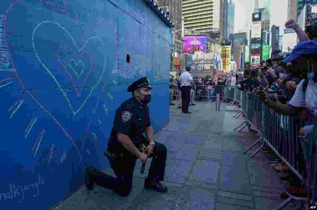 A New York City police officer takes a knee during a demonstration by protesters in Times Square, May 31, 2020, over the death of George Floyd in police custody.